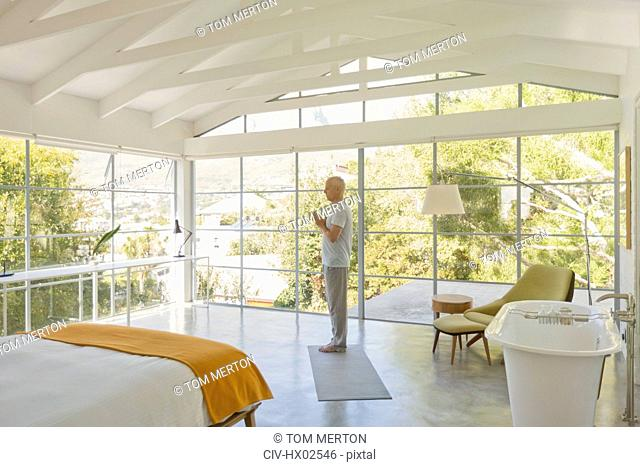 Mature man practicing yoga with hands at heart center in modern bedroom with vaulted wood beam ceilings