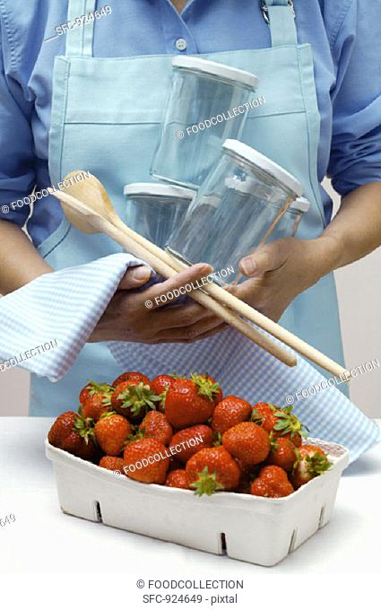 Woman with preserving jars, kitchen spoons & strawberries