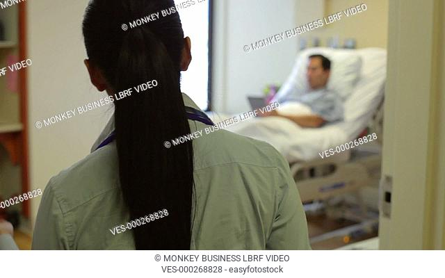 Male patient using digital tablet is visited by female consultant who gives him good news.Shot on Sony FS700 in PAL format at a frame rate of 25fps