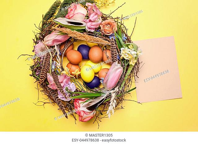 Easter card. Painted Easter eggs in nest on yellow table background. Top view of easter decoration. Happy easter concept