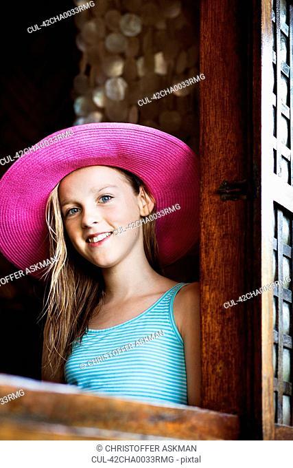 Girl wearing straw hat at window