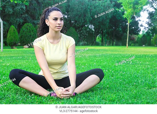 Portrait of calm and beautiful female athlete stretching legs in park of Cordoba,Spain
