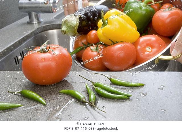 Close-up of person's hands holding vegetables under running water in a colander