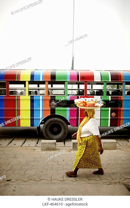 Merchant passing a school bus, Cotonou, Littoral Department, Benin
