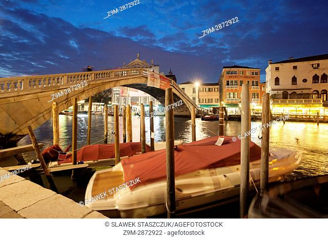 Night falls at Scalzi bridge across Grand Canal in Venice, Italy
