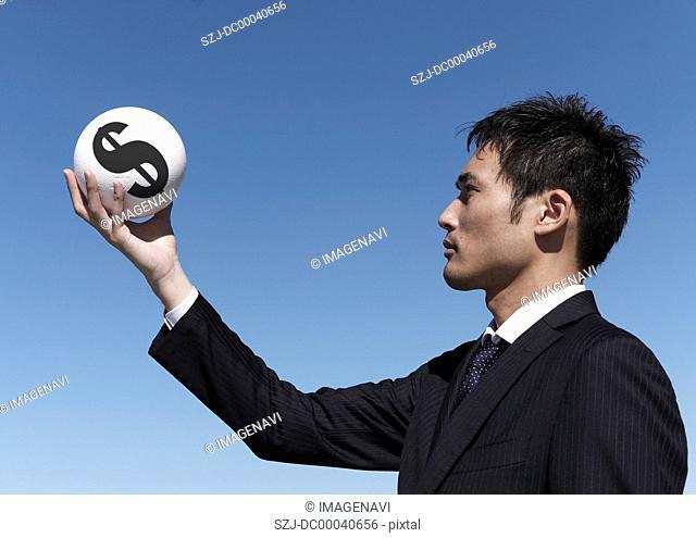 Businessman holding dollar sign ball