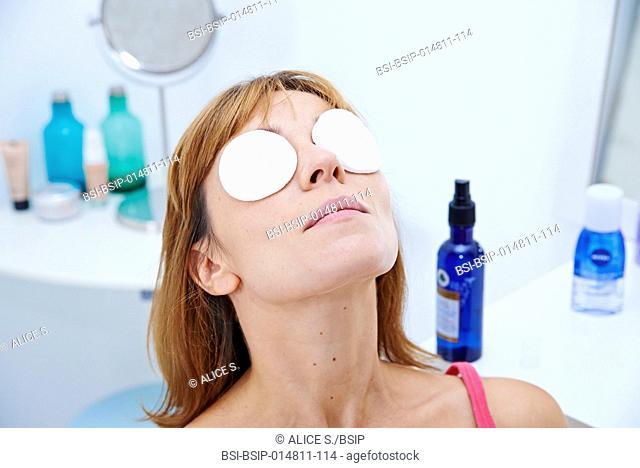 Woman applying cornflower floral water on her eyes