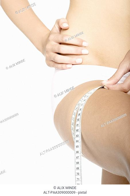 Woman measuring thigh, close-up