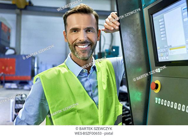 Portrait of smiling engineer next to computer in factory
