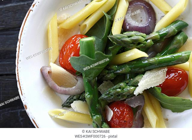 Close up of noodle salad with ruccola, asparagus, parmesan and cherry tomatoes