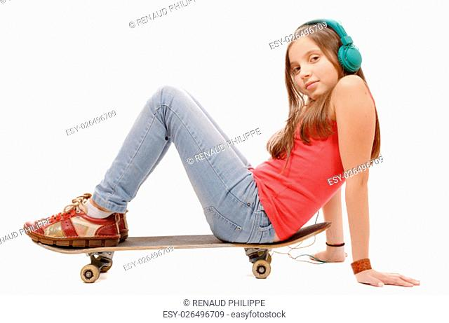 a pretty young girl sitting on skateboard, listen a music