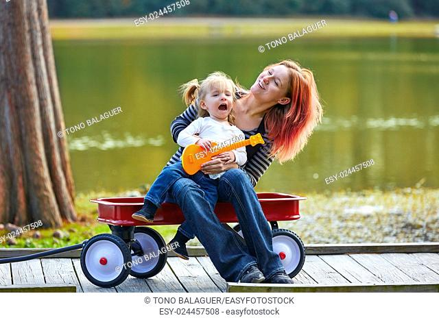 mother and daughter playing toy guitar singing in the park lake with pull cart