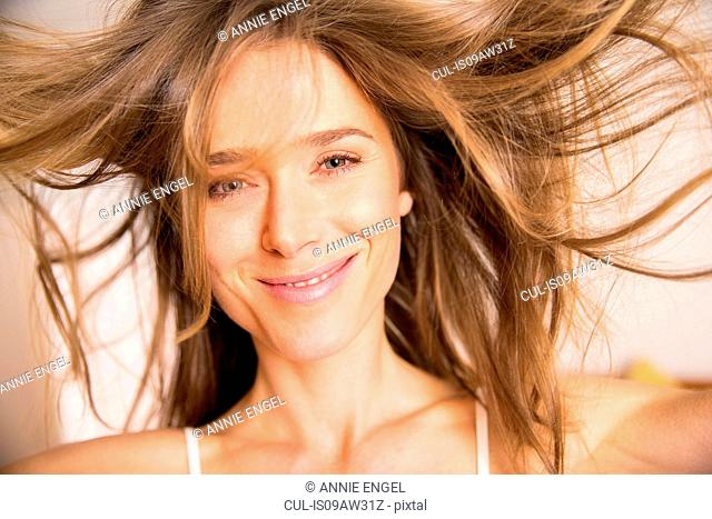 Portrait of happy woman with flyaway long blond hair
