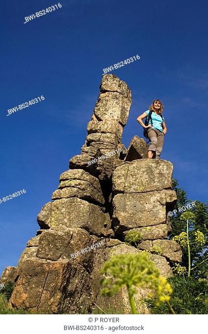 woman standing on a bizarrely shaped rock needle enjoying the sight, France, Cevennes National Park