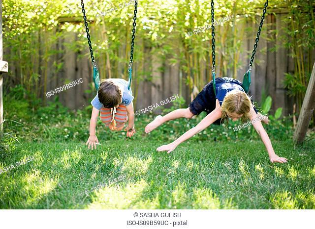 Boy and girl lying on fronts swinging on garden swings