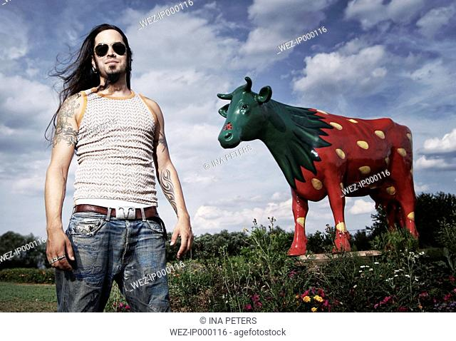 Portrait of a cool guy in front of a painted strawberry cow