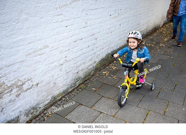 Daughter riding bicycle with training wheels