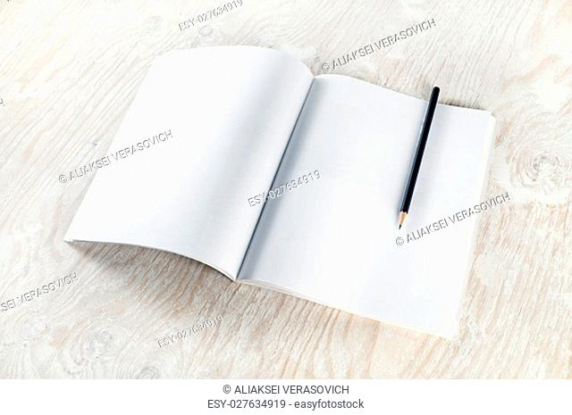 Blank opened brochure with a pencil on light wooden table background. Mockup for placing your design. Top view