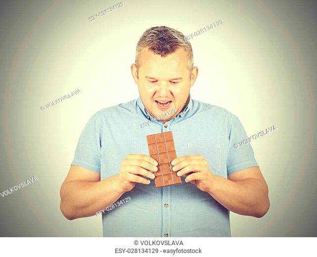 fat man wants to take a bite of chocolate. Diet, overweight, healthy food isolated on background