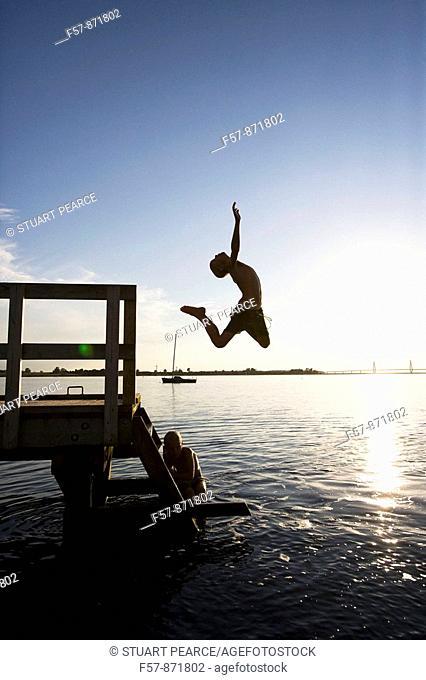 Boys leaping off a pier in Denmark