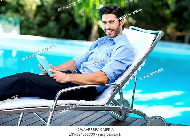 Smart man using digital tablet near pool