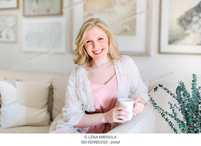 Young woman sitting on sofa holding coffee mug, portrait