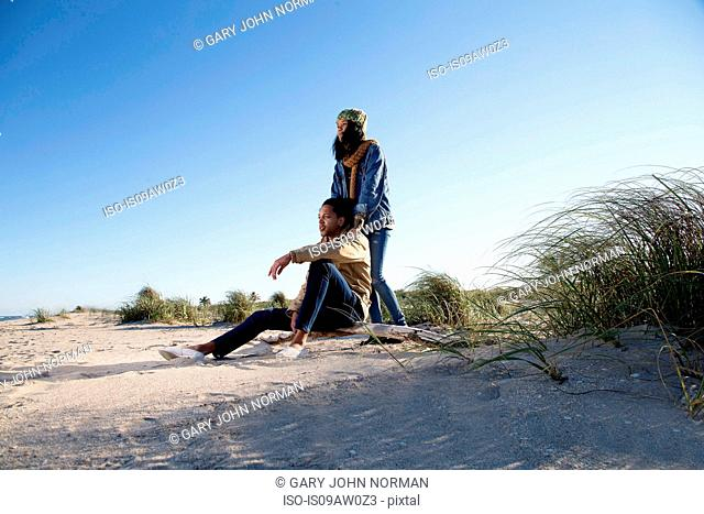Young couple relaxing on beach, looking at view