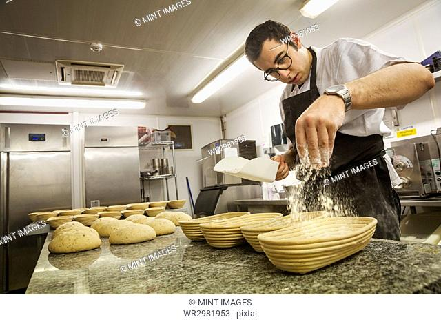 Baker sprinkling flower on bread dough and proving baskets in the kitchen