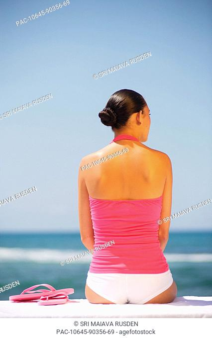 Hawaii, Oahu, Attractive young woman in bright colors sits by turquoise ocean