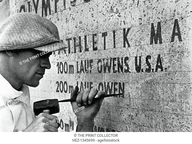 Berlin Olympics, 1936. Jesse Owens' name being inscribed on the monument listing gold medal winners. A print from Olympia 1936, Die Olympischen Spiele 1936