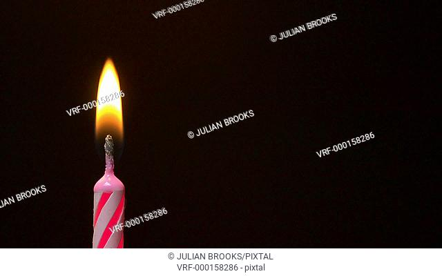 pink birthday candle being blown out close up - slow motion 2
