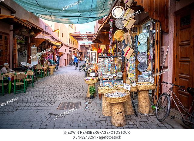Market stalls selling handcrafted goods and souvenirs line either side of narrow street in medina quarter of Marrakesh, Morocco