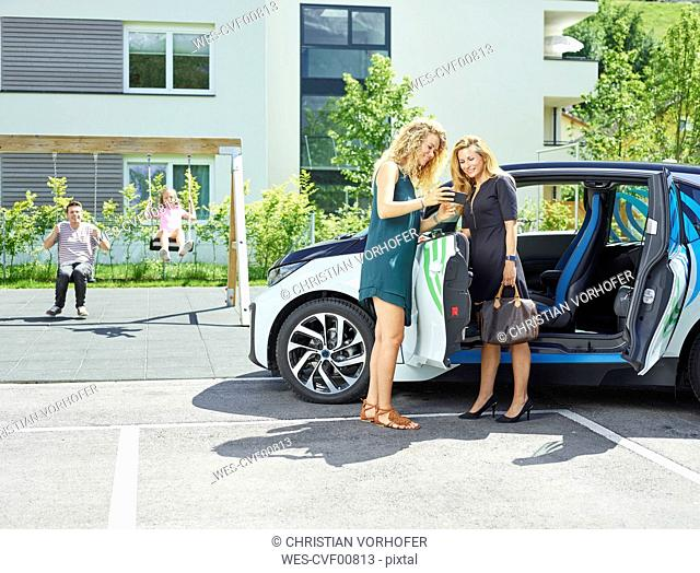Two women with cell phone at electric car and man and girl in background