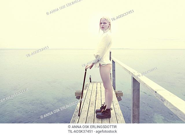 Female teenager with blonde hair standing by sea on wooden jetty
