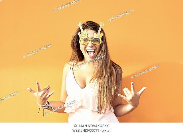 Portrait of smiling young woman with guitar sunglasses in front of orange background