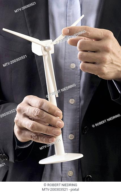 Businessman examining wind turbine model, Bavaria, Germany