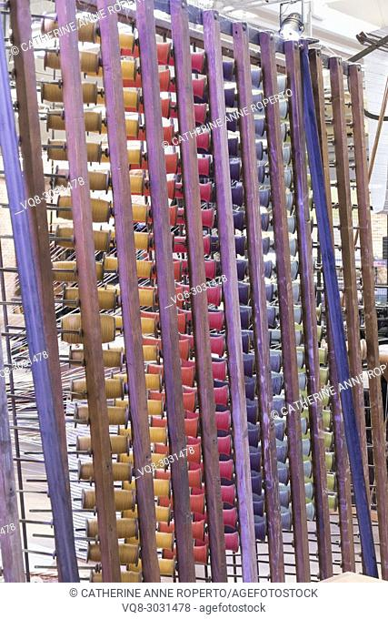 Racks of repeating rainbow coloured threads on wooden reels in traditional jacquard weaving industry, La Manufacture de Roubaix, France