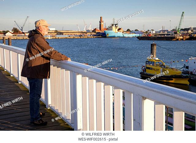 Germany, Lower Saxony, Cuxhaven, senior at harbor looking at view