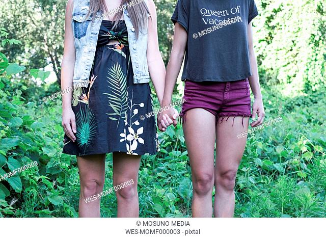 Two fashionable female friends standing hand in hand, partial view