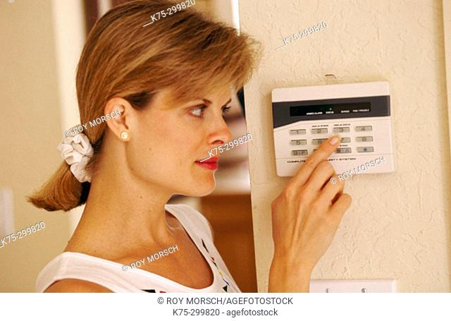 woman at her home alarm system