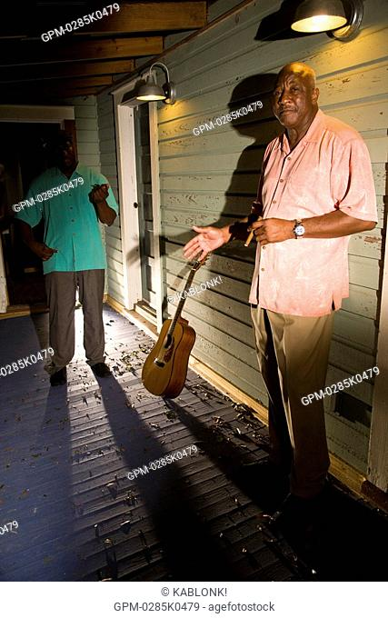 Portrait of African American Blues musicians standing on porch of house