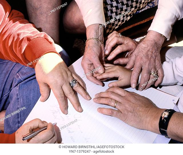 close up of a group of female hands of all ages working on a group project and taking notes in a diary