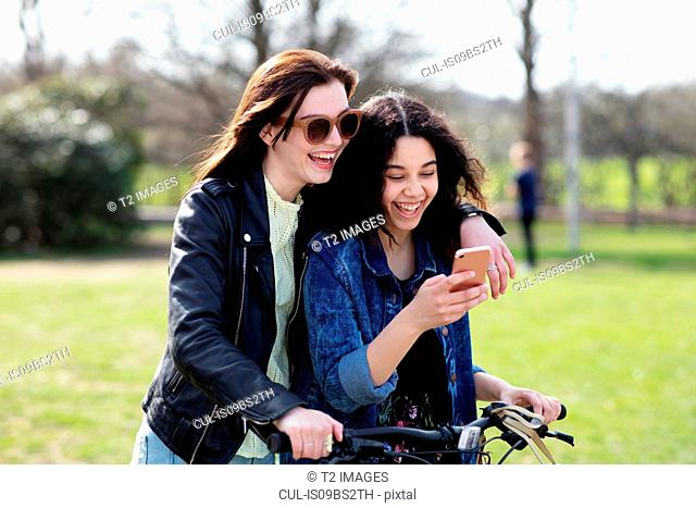Teenage girls reading text together on push bike