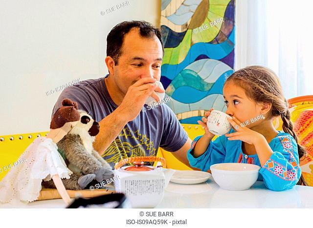 Mature man, and daughter sharing tea