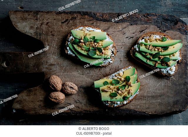 Still life of ricotta, avocado and walnut bruschetta on chopping board, overhead view