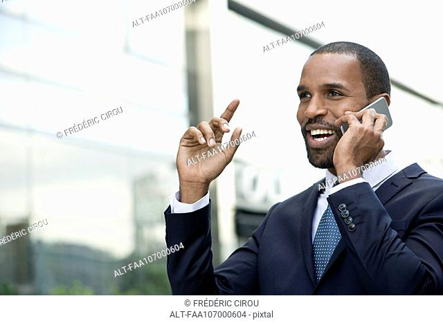 Businessman talking and laughing on cell phone