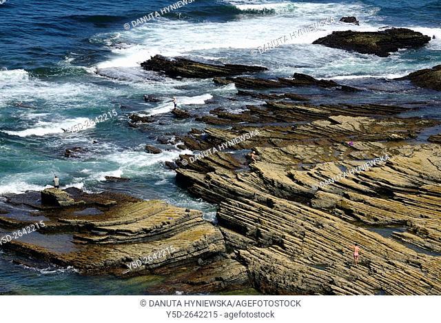 Europe, Portugal, Algarve, Faro district, Azjezur, Costa Vicentina, Monte Clérigo beach, Praia do Monte Clérigo, few people on almost empty rocks