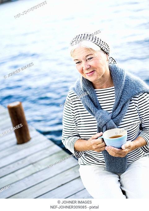 An older woman drinking tea outside