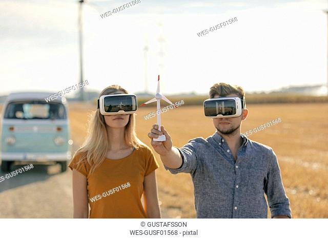 Young couple with VR glasses at camper van in rural landscape holding wind turbine model