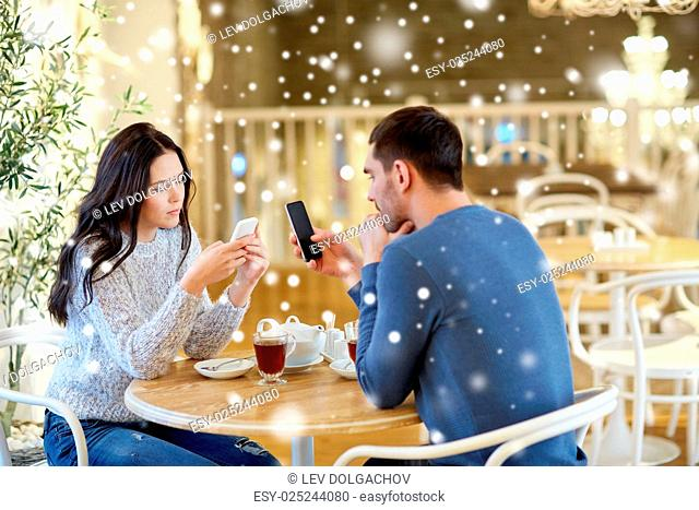 people, communication and dating concept - couple with smartphones drinking tea at cafe or restaurant